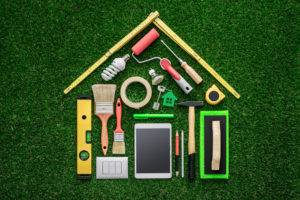 Home renovation remodeling and DIY concept work tools and tablet composing a house shape on the grass