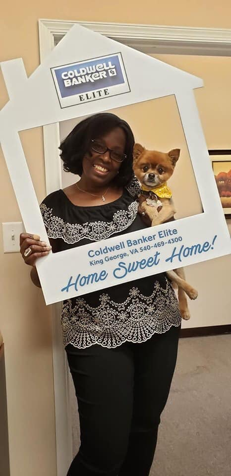 female real estate agent with pomeranian dog in coldwell banker elite office
